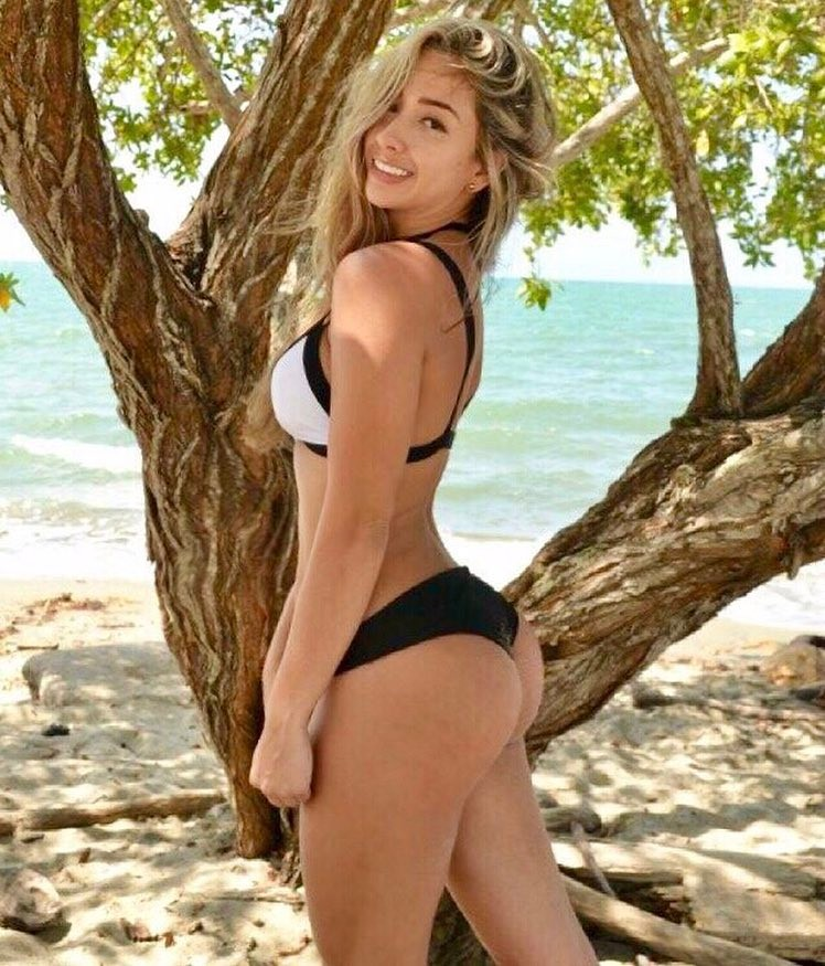 Luisa Polo posing on a beach by a tree showing off her curvy legs and glutes
