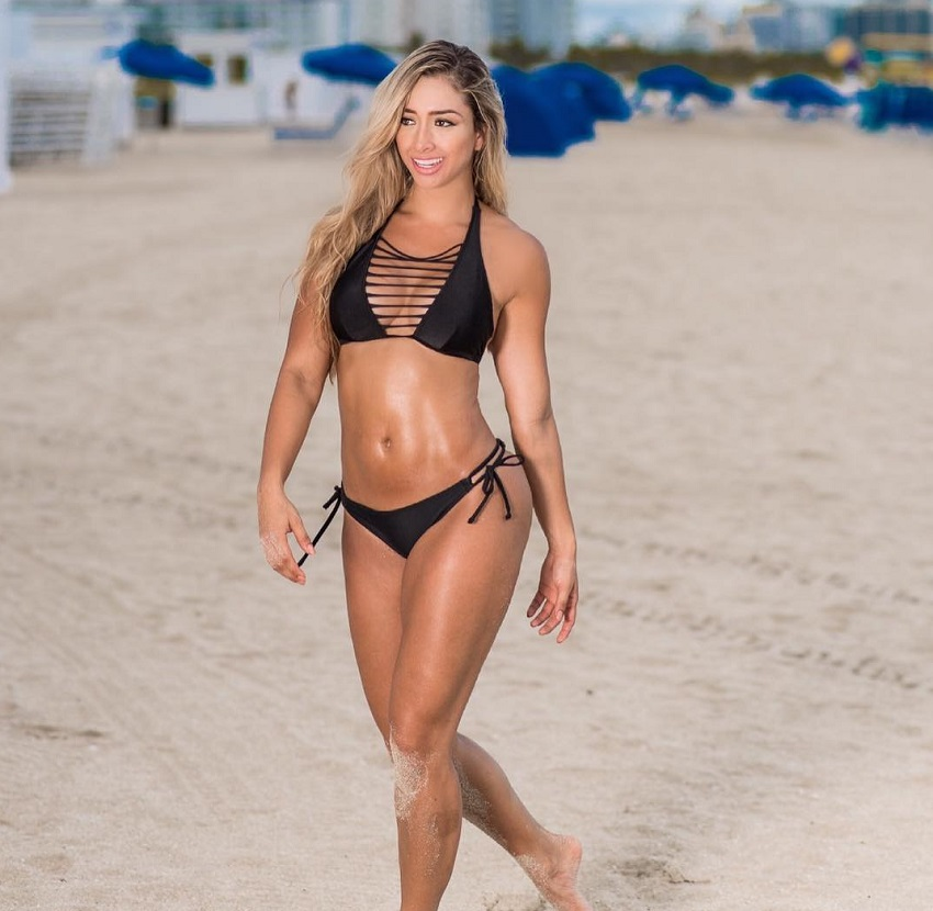 Luisa Polo walking on a sand beach looking fit and curvy