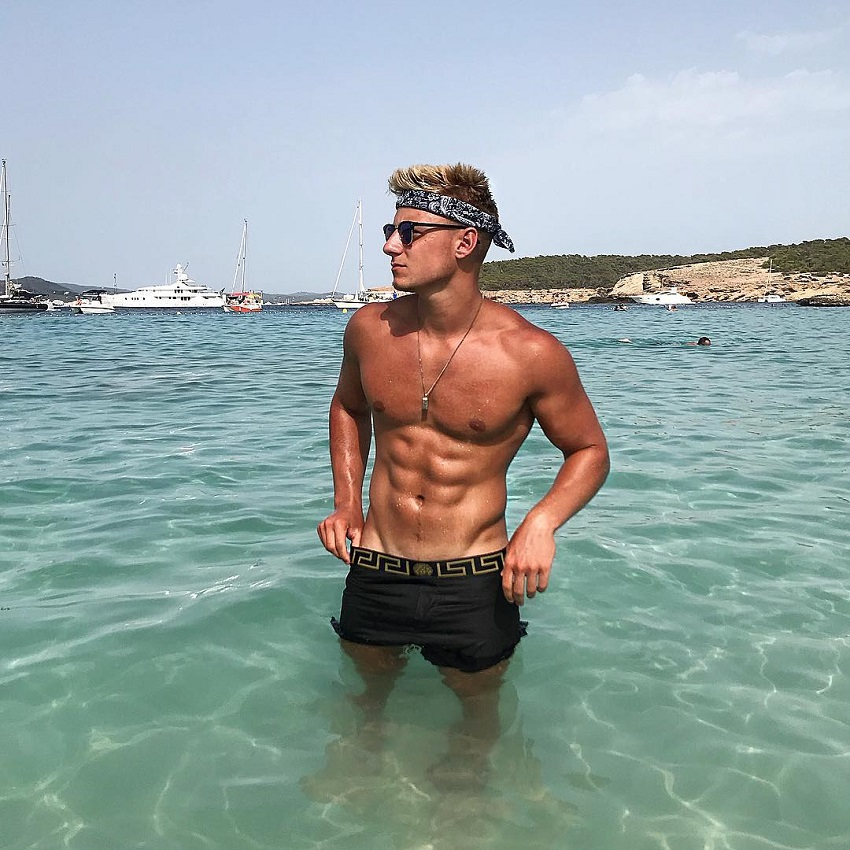 Max Wyatt standing shirtless in the sea looking strong and ripped