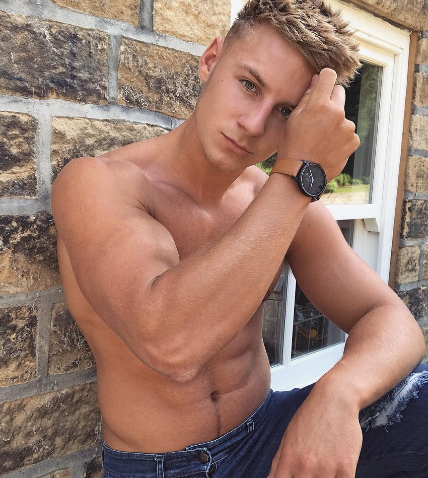Max Wyatt posing shirtless for a photo displaying his muscular arms