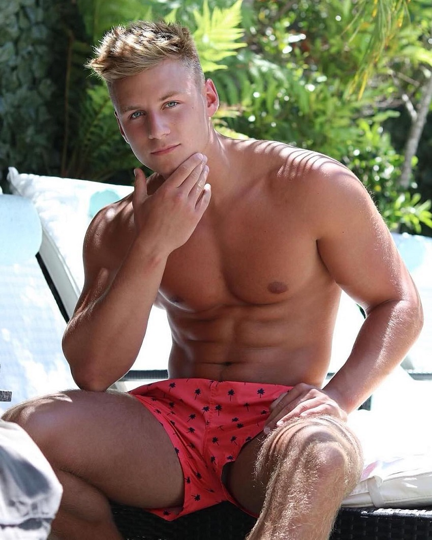 Max Wyatt sitting shirtless showcasing his chiseled midsection