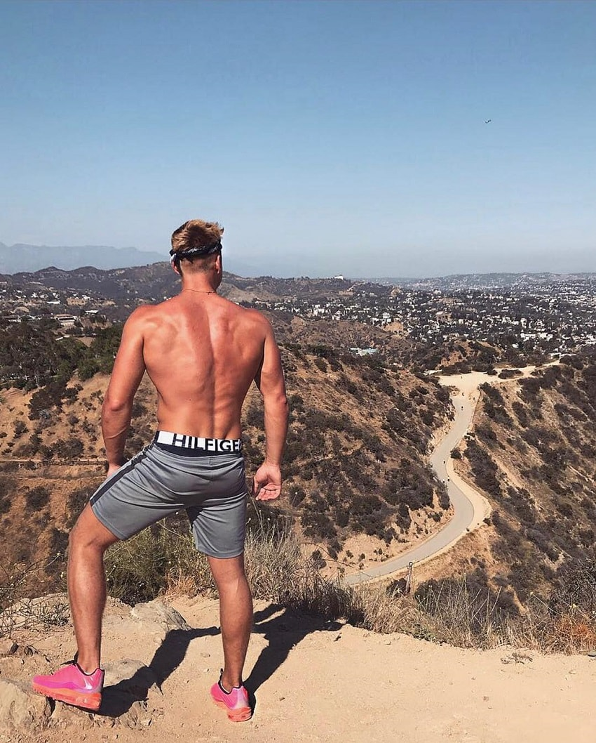 Max Wyatt standing shirtless on a hill looking strong and fit