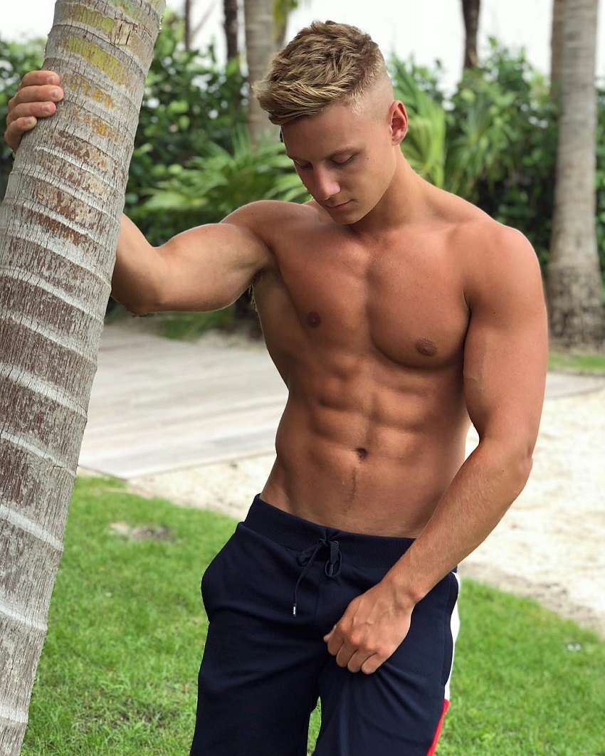 Max Wyatt posing by a tree looking lean and fit