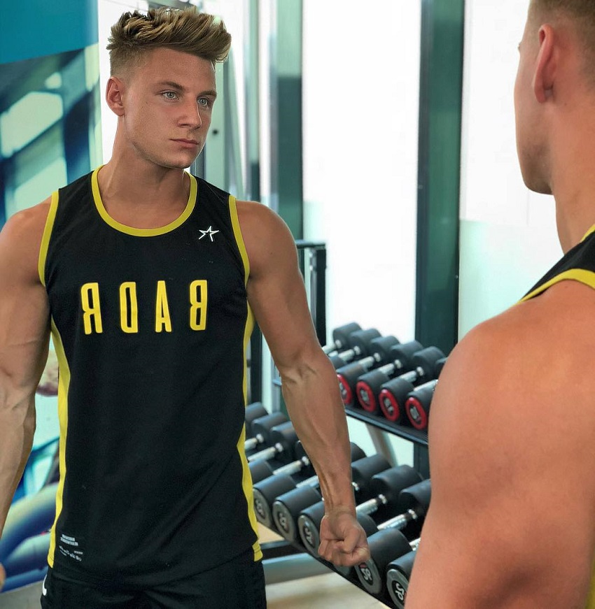 Max Wyatt looking at himself in the mirror in the gym