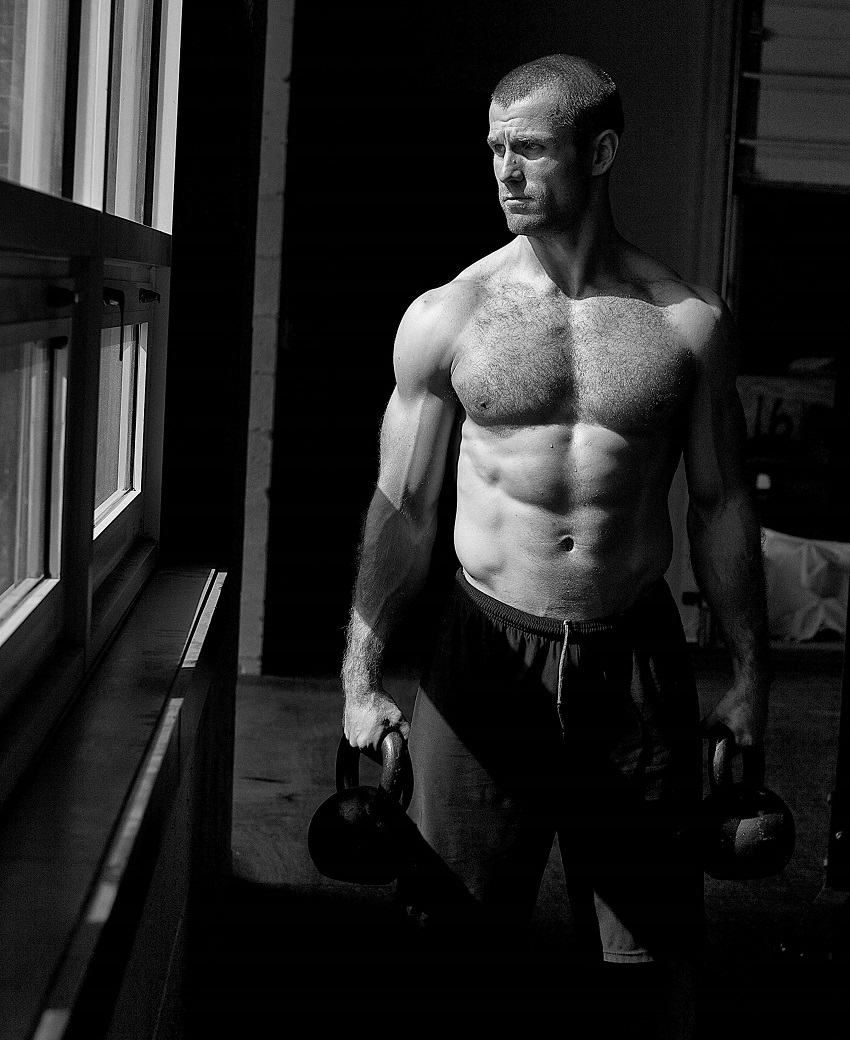 Mikko Salo standing shirtless and looking through the window