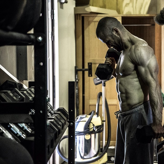 Mikko Salo lifting heavy dumbbells in a gym looking fit and strong