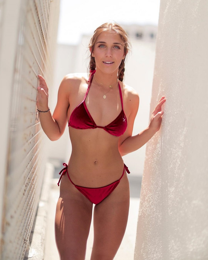 Mitch Fit posing for a photo in her red bikini looking fit and lean