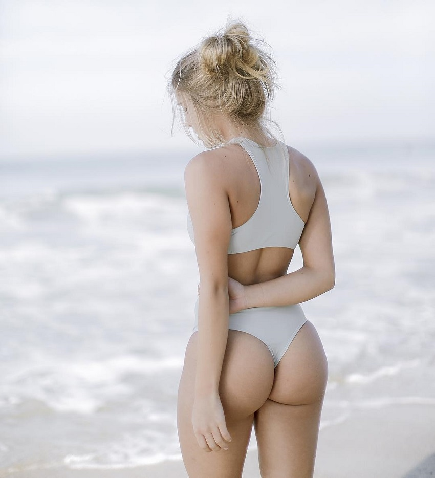 Mitch Fit standing on the shore showing off her curvy glutes