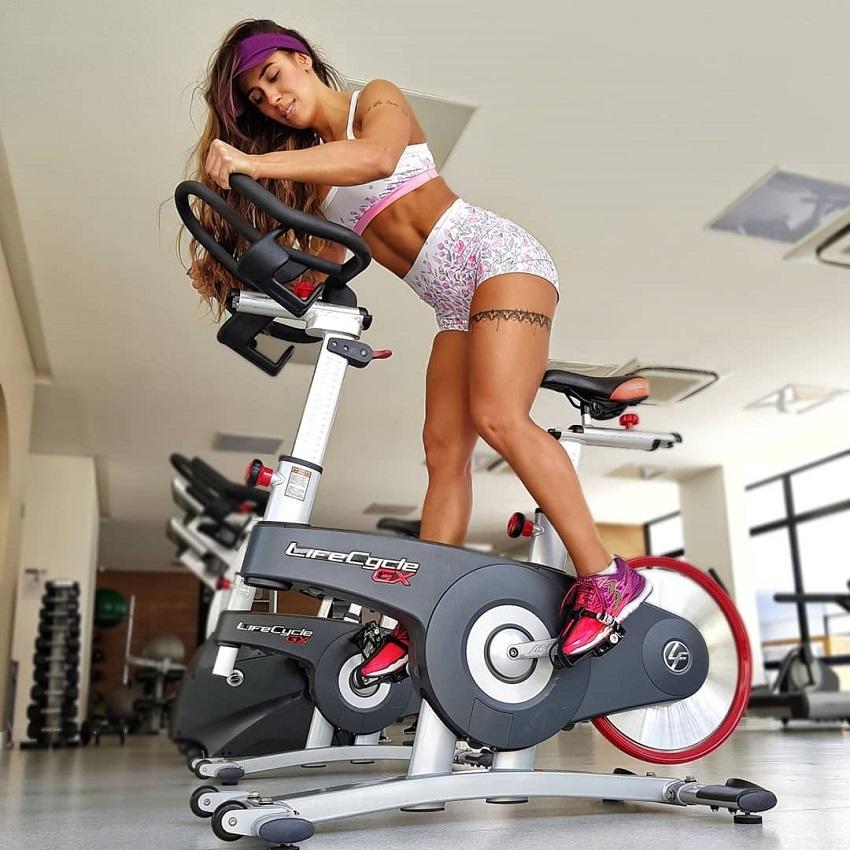Natalia Carvalho doing cardio on a stationary bike