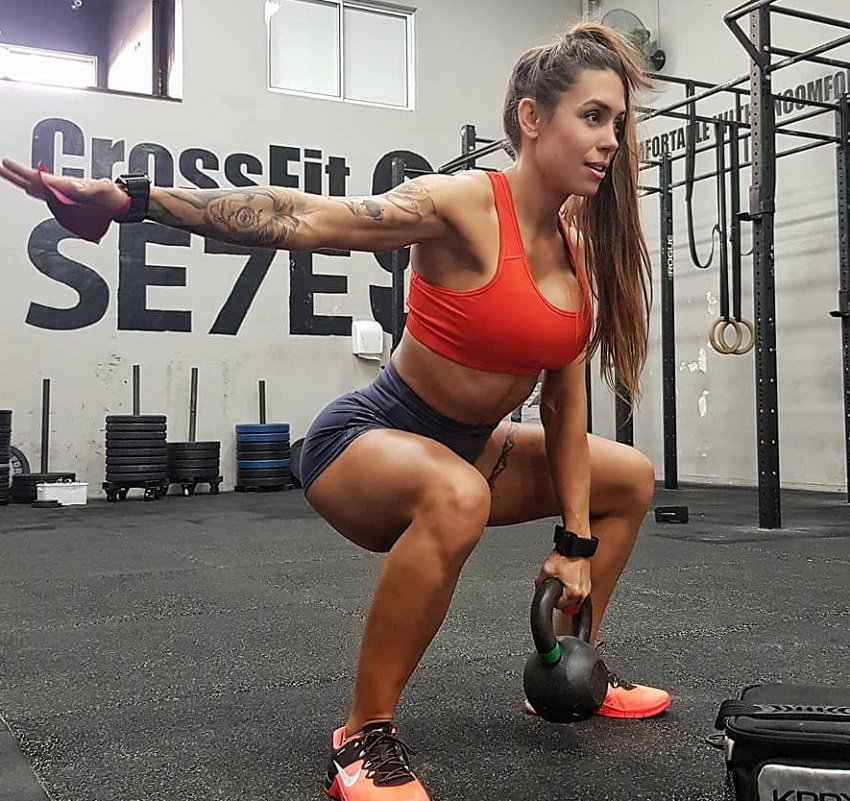 Natalia Carvalho performing a kettlebell exercise in the gym
