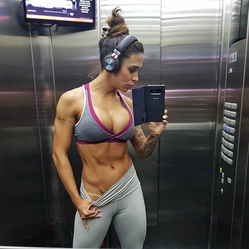 Natalia Carvalho taking a selfie in the elevator looking ripped and fit