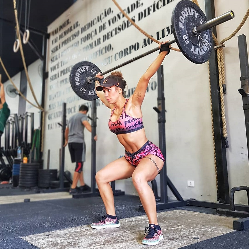 Natalia Carvalho doing an overhead barbell press looking strong