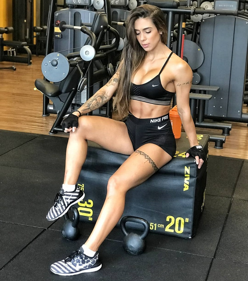 Natalia Carvalho posing for a photo in the gym looking fit and lean