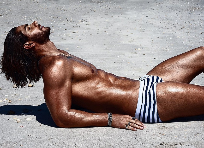 Paul Iskandar lying shirtless on the beach