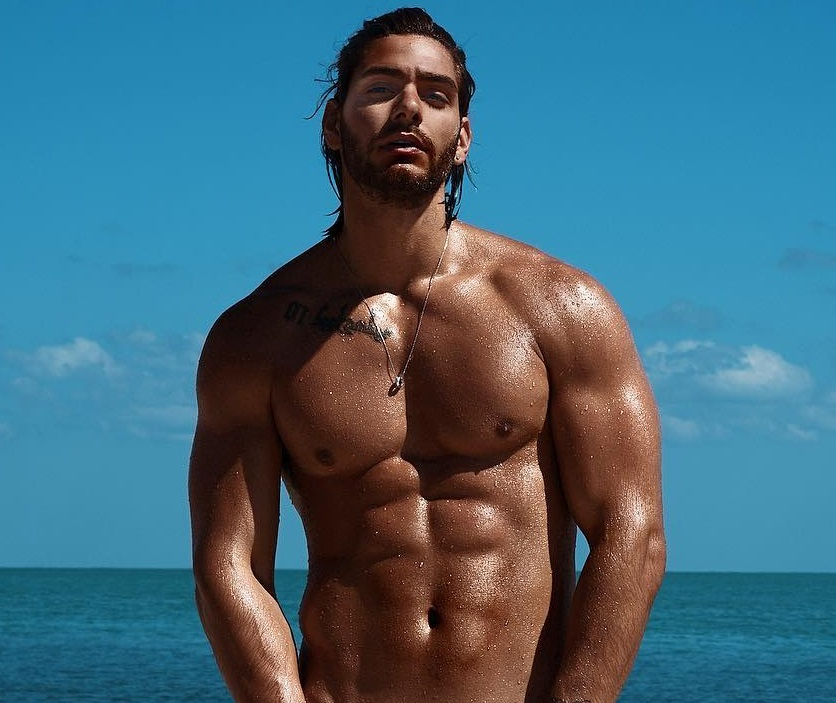 Paul Iskandar posing shirtless by the sea looking ripped