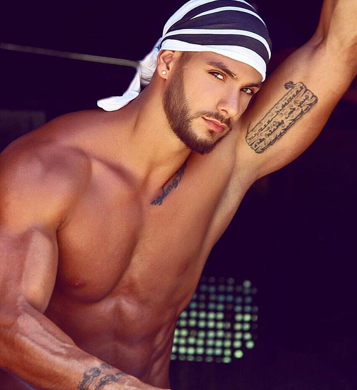 Paul Iskandar posing shirtless with a bandana on his head, looking fit and strong