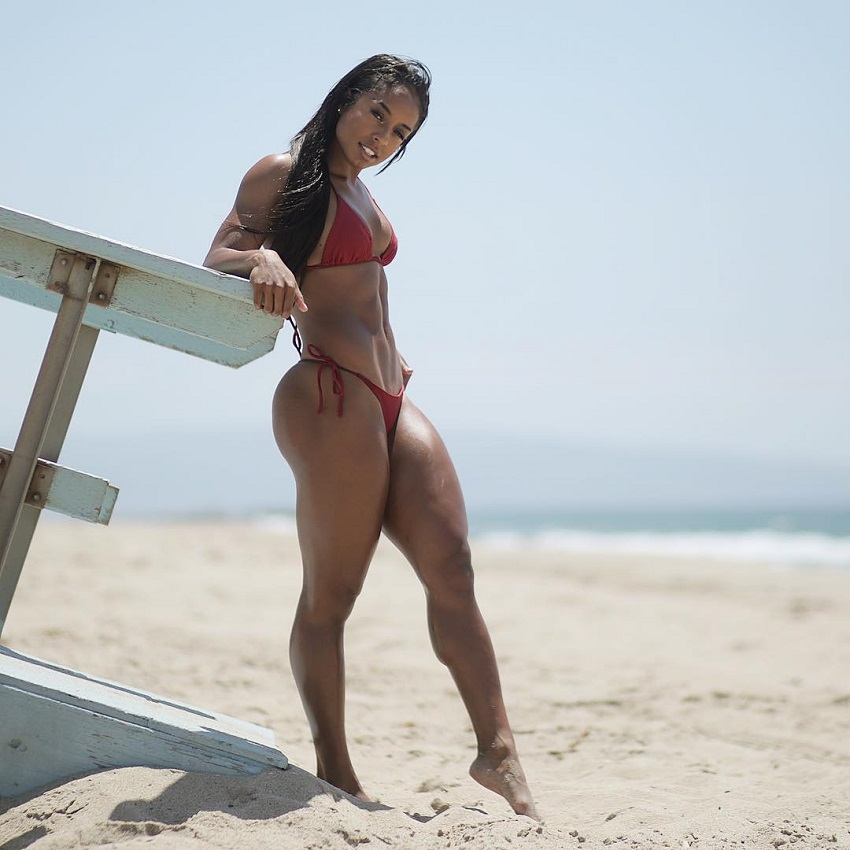 Qimmah Russo standing on the beach in a bikini looking fit and strong
