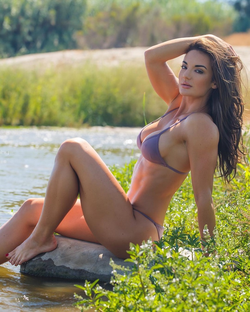 Whitney Johns sitting on grass by a river looking fit