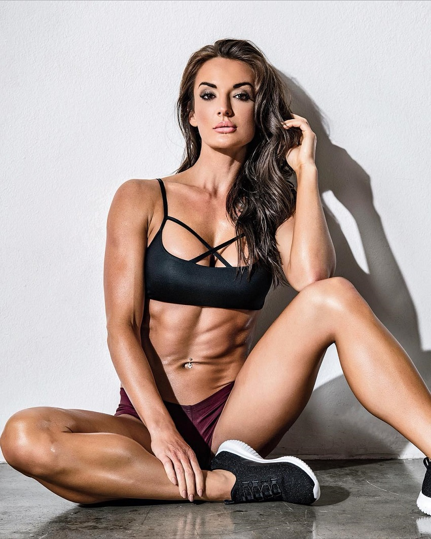 Whitney Johns posing for a photo while sitting on a floor looking lean and toned