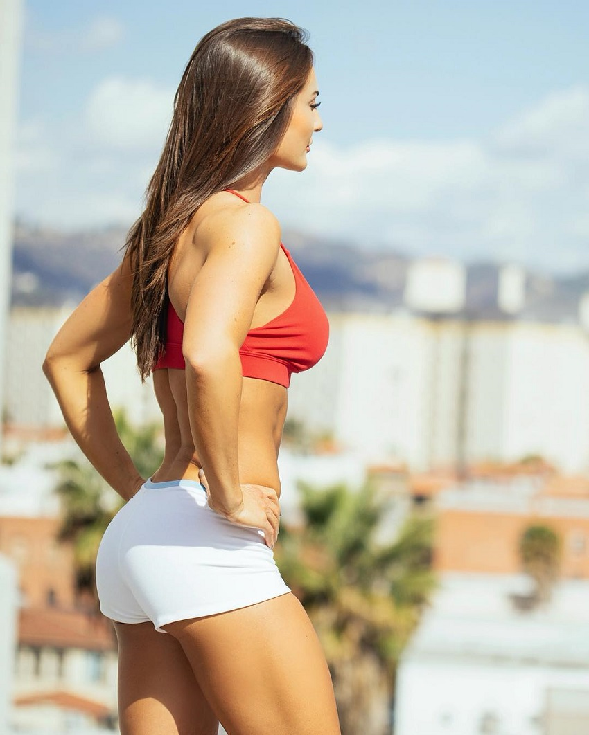 Whitney Johns posing for a photo in her sportswear showcasing her toned legs and glutes