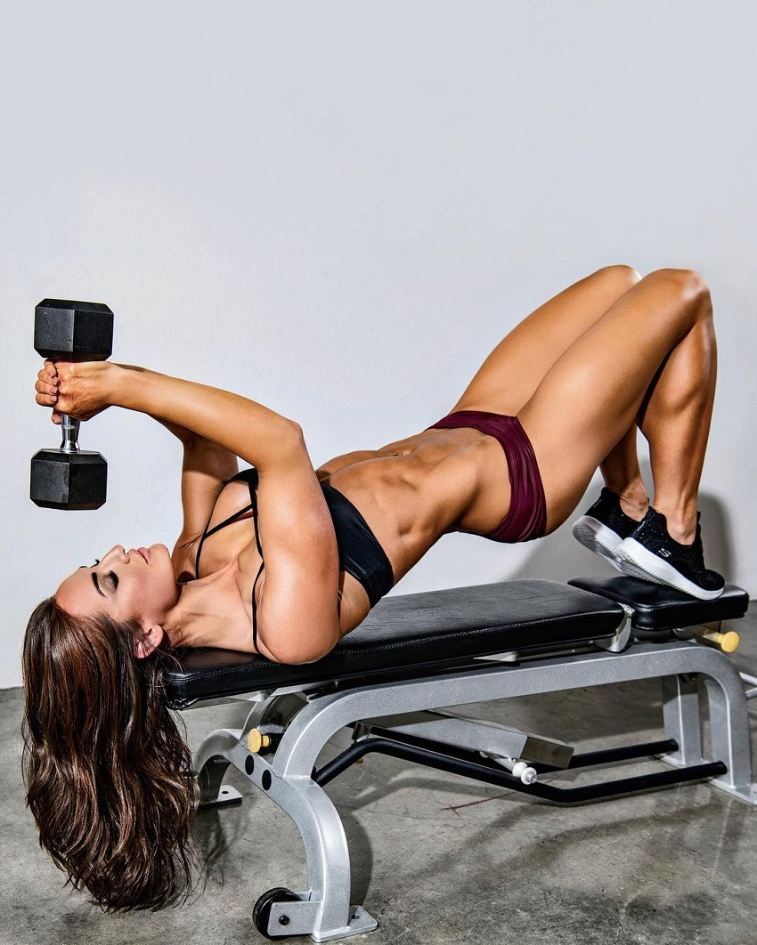 Whitney Johns doing an exercise with a dumbbell while lying on a bench
