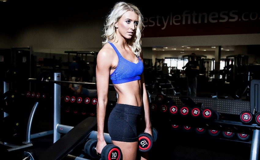 Zanna Van Dijk holding dumbbells in her arms looking lean