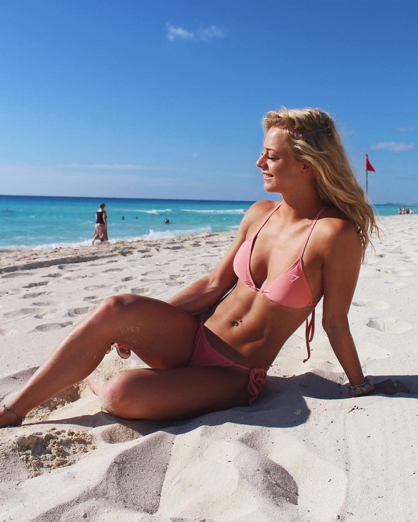 Becca Louise Sills showcasing her lean abs on the beach
