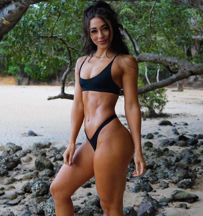 Danielle Robertson posing for a photo in a black bikini looking fit and ripped