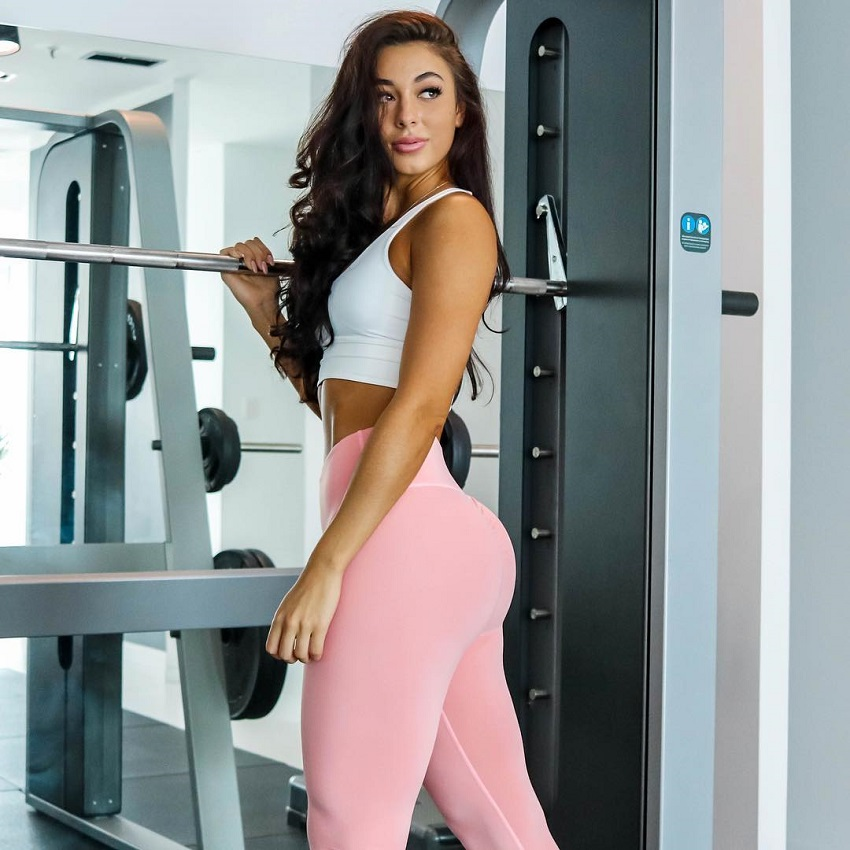 Danielle Robertson standing by a squat rack wearing pink leggings