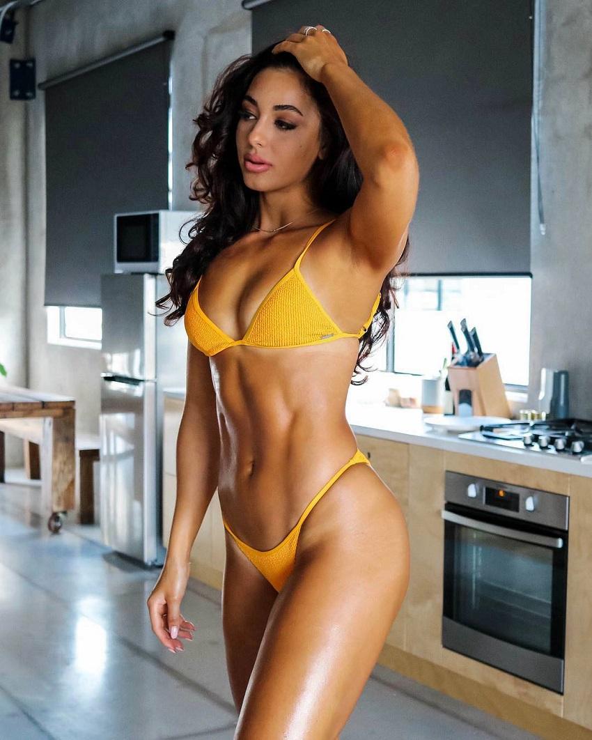 Danielle Robertson posing in a yellow bikini looking fit and lean