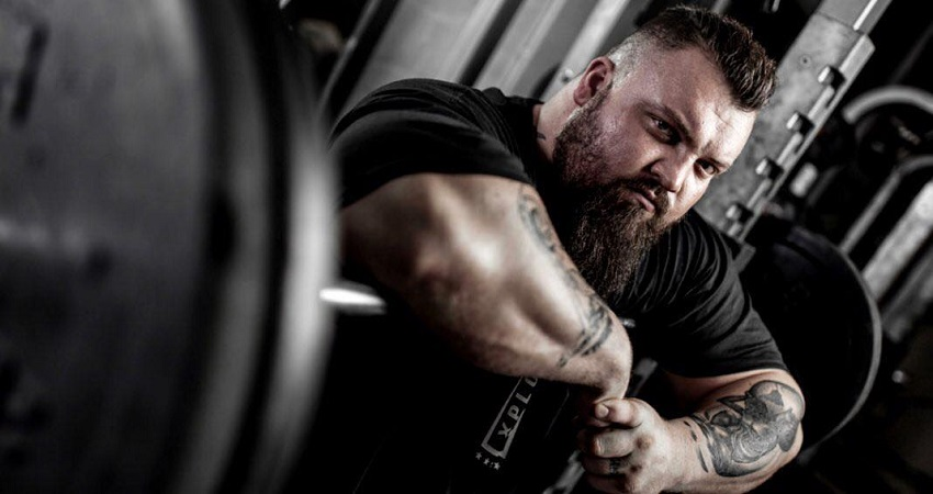 Eddie Hall posing for the camera leaning against a barbell loaded with weights