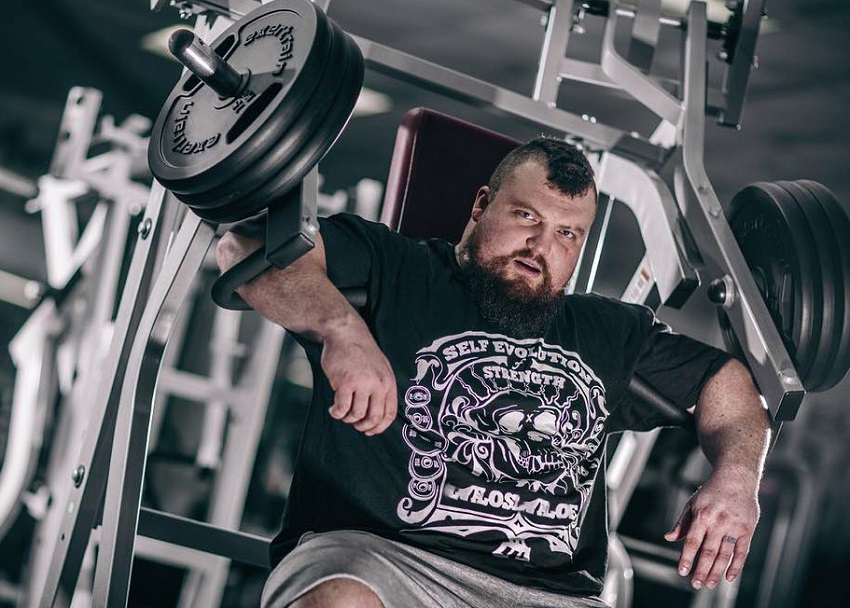 Eddie Hall resting on a chest machine looking big and strong