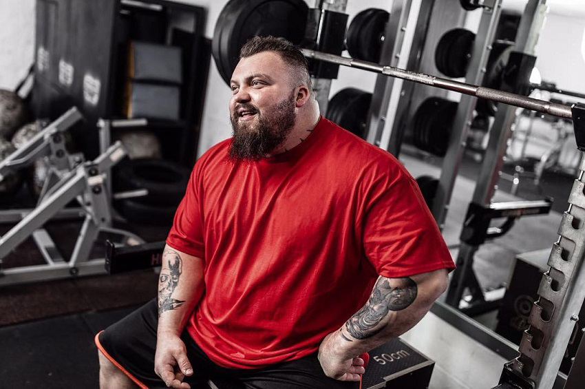 Eddie Hall sitting by the bench press in his red shirt looking big and strong