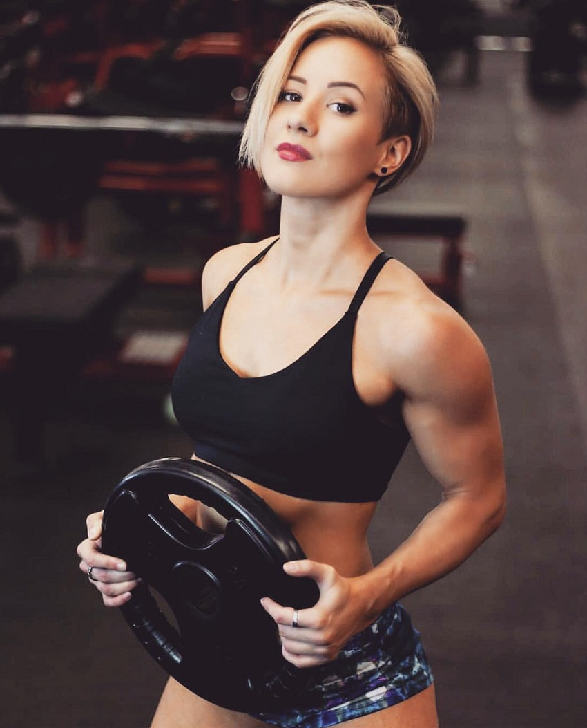 Elena Soboleva posing in a photo shoot with a weight plate in her hands