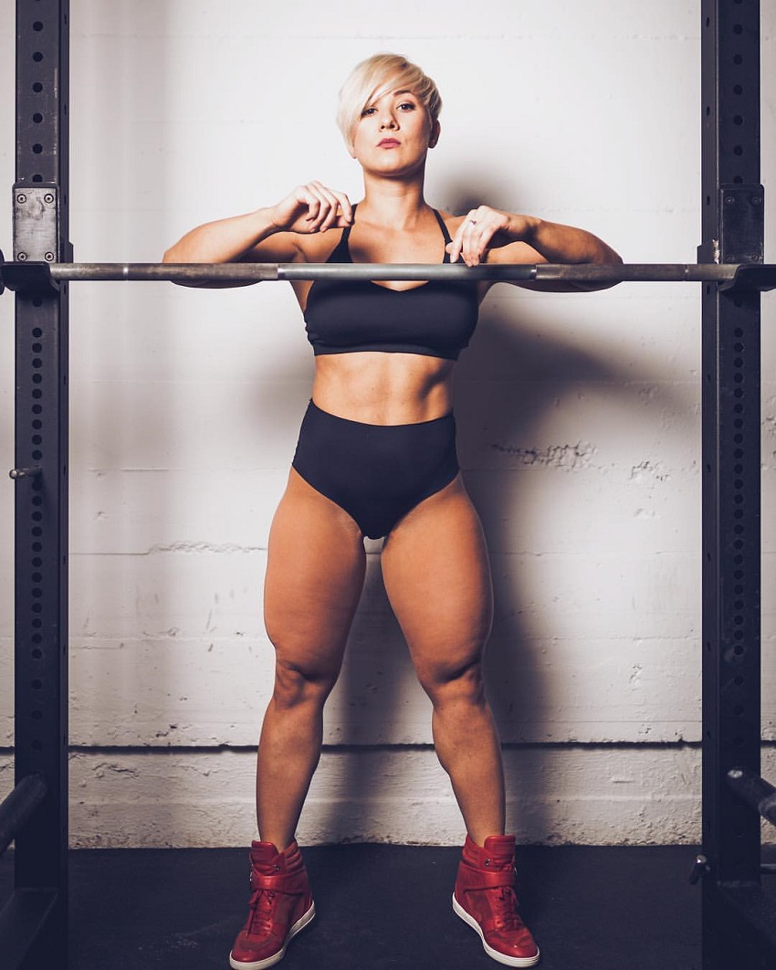 Elena Soboleva posing by a barbell showing off her curvy and strong legs