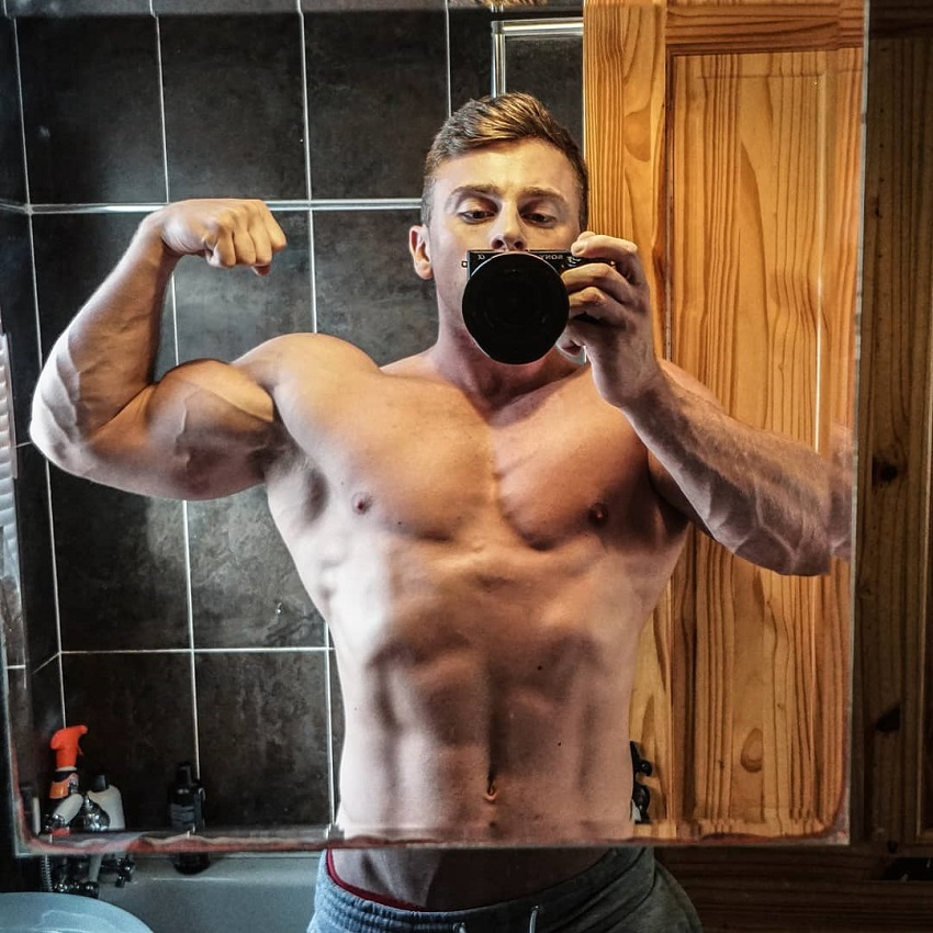 Glen Gillen flexing his biceps for a photo looking strong and lean