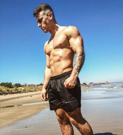 Glen Gillen posing shirtless on a beach looking muscular