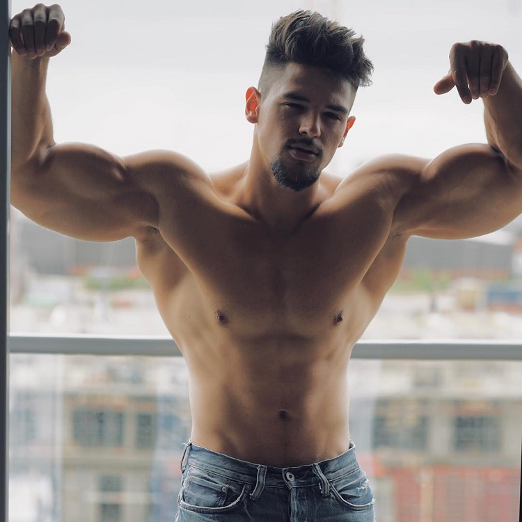 Jamar Pusch flexing his muscles on a balcony