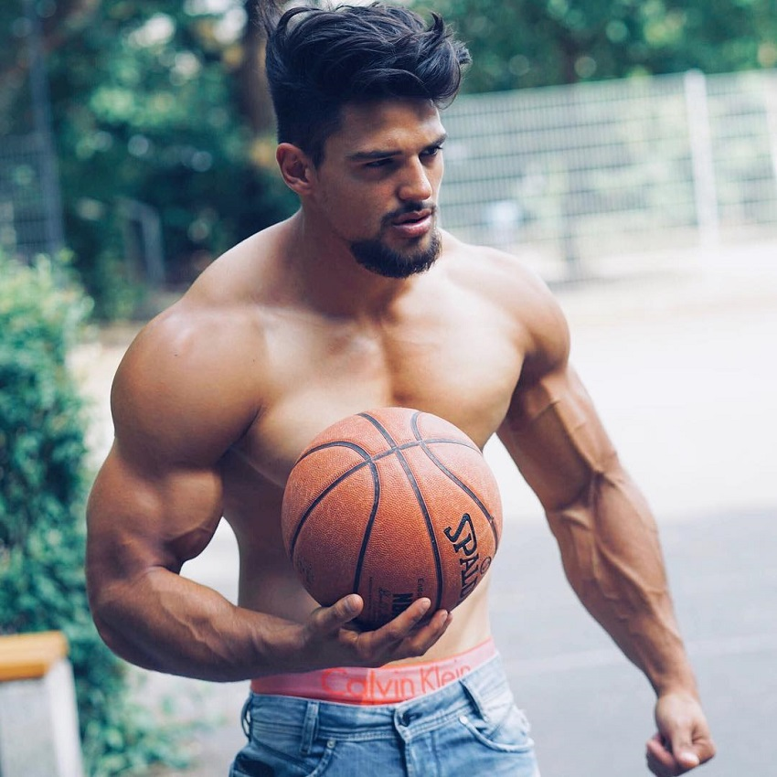 Jamar Pusch holding a basketball in his hands while standing shirtless