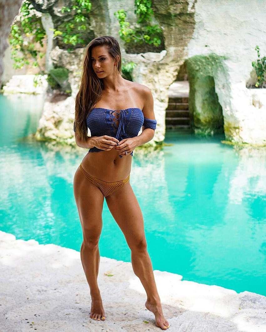 Janna Breslin standing by the pool in an exotic dress looking fit and toned