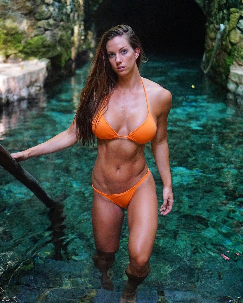 Janna Breslin standing in the pool in her orange bikini showing off her lean and fit body