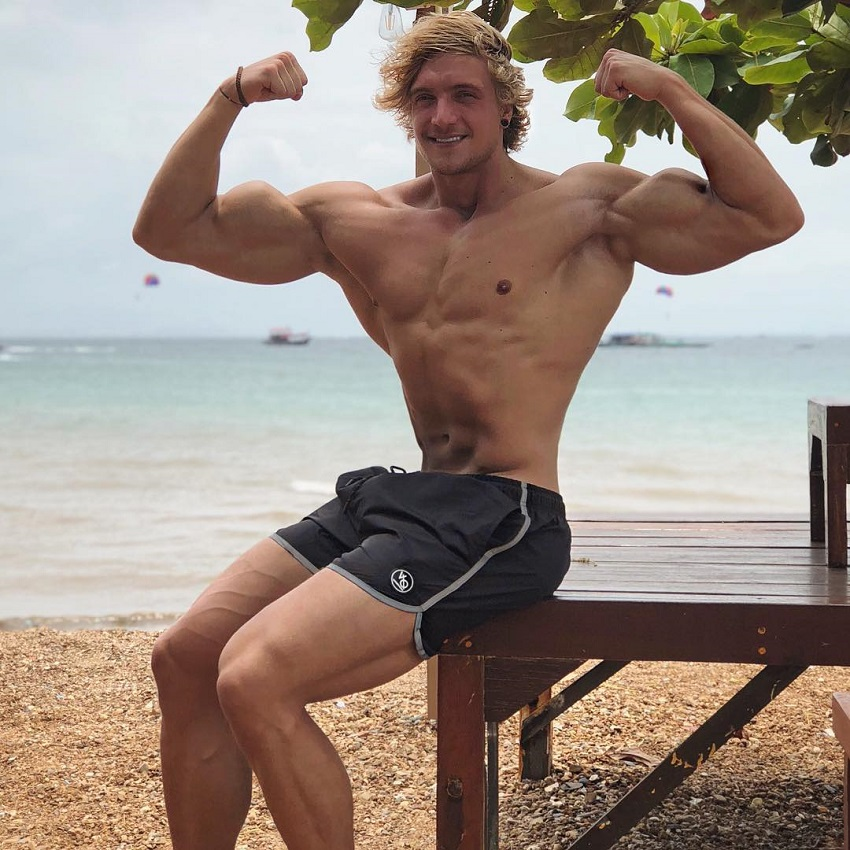 Jo Linder flexing his arms on the beach looking aesthetic and strong