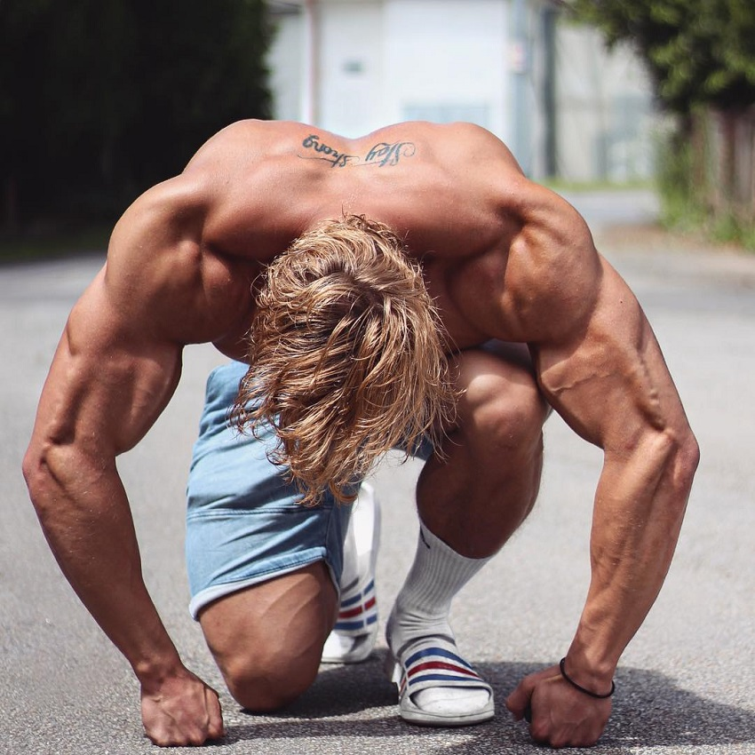 Jo Linder posing shirtless on the ground looking ripped and strong