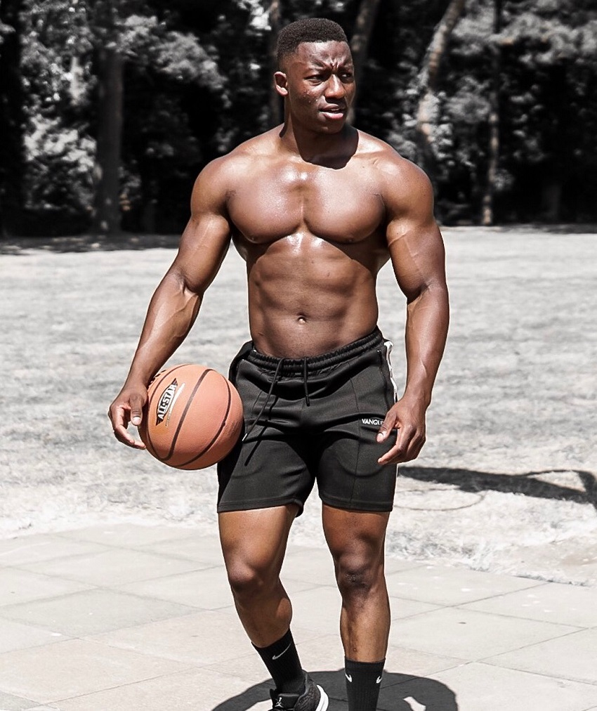 Lubomba Munkuli holding a basketball while shirtless, looking strong and ripped