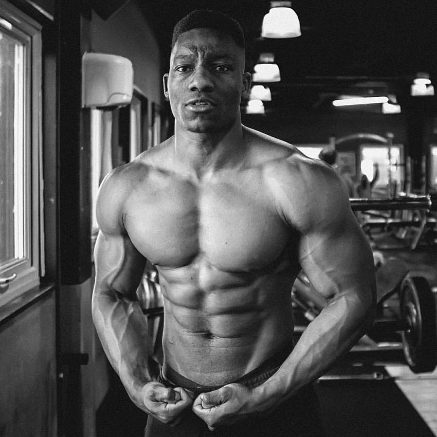 Lubomba Munkuli flexing shirtless in a black and white photo