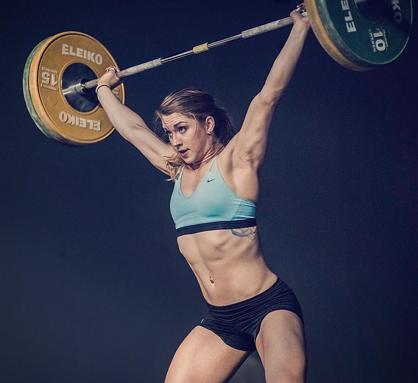 Mattie Rogers doing a heavy overhead press during a weightlifting contest
