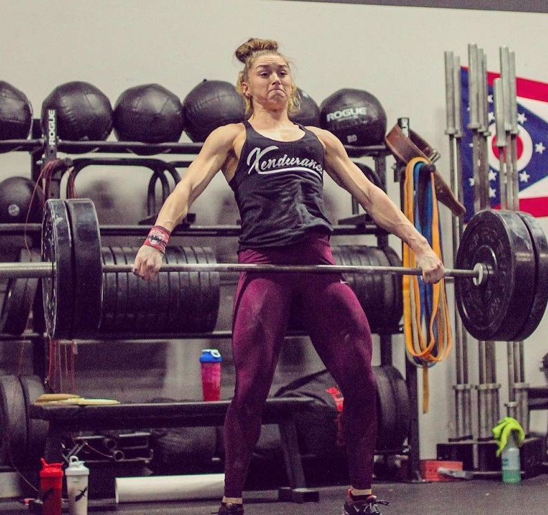 Mattie Rogers lifting an extremely heavy barbell loaded with weights during training