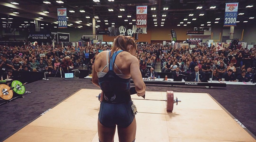 Mattie Rogers standing on the stage in front of a huge audience during a weightlifting contest