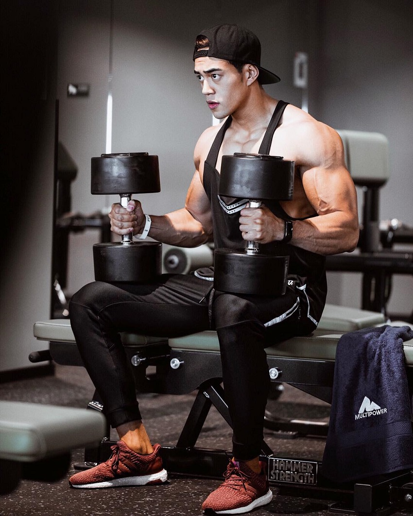Nam Vo sitting with dumbbells looking strong and fit