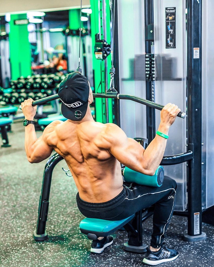 Nam Vo performing lat pulldowns shirtless, looking muscular and ripped